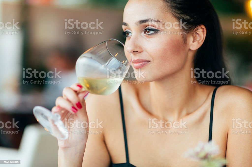 Attractive woman tasting white wine stock photo