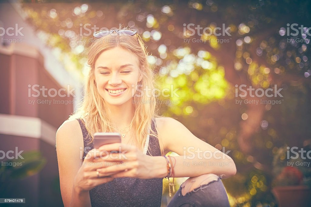 Attractive woman texting on smart phone stock photo