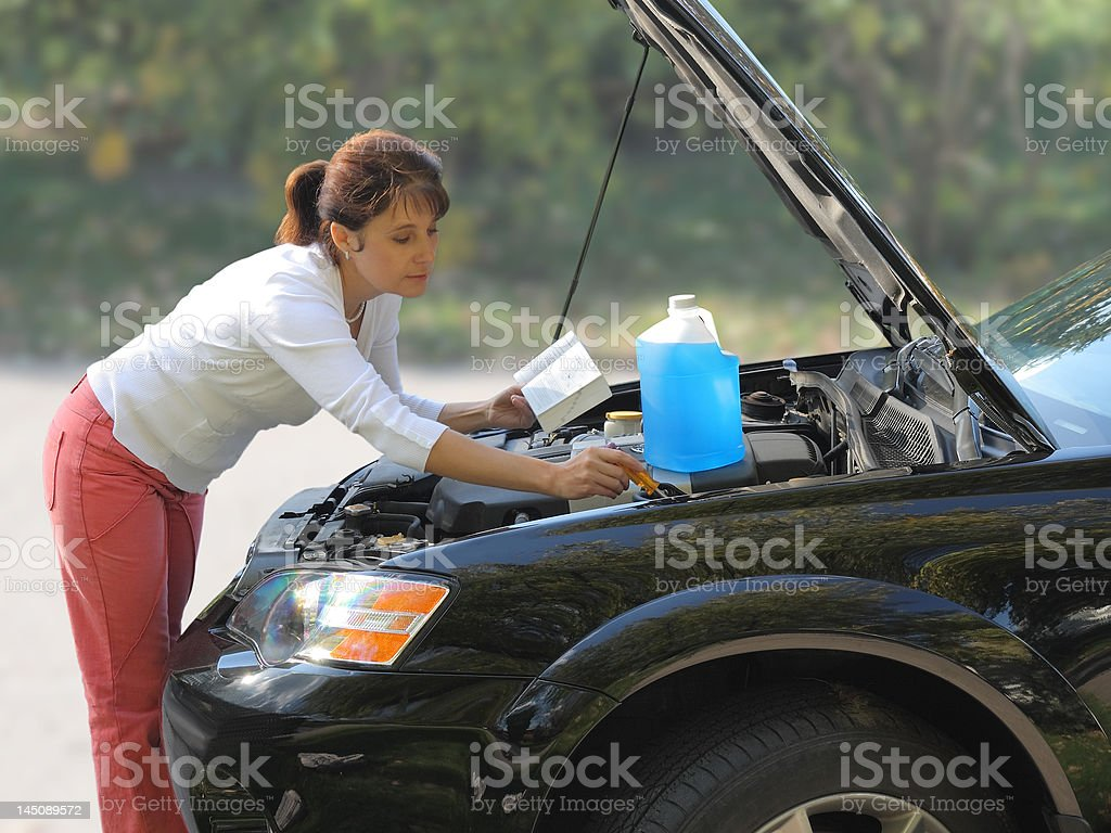 Attractive woman trying to fix the car royalty-free stock photo