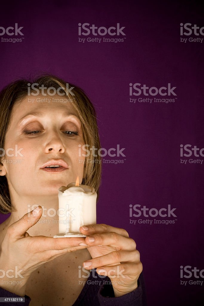 Attractive woman turn off a candle stock photo