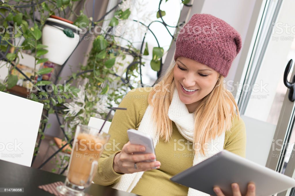 Attractive woman using digital tablet and smart phone at cafe stock photo