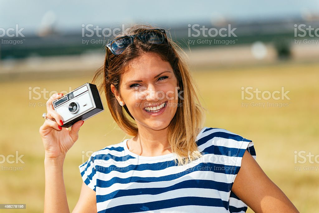 Attractive woman using vintage camera and photographing nature stock photo
