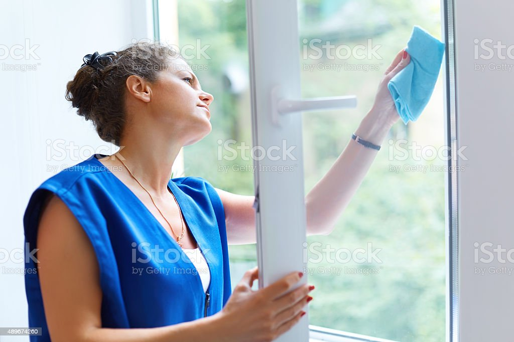 Attractive Woman Washing the Window. Cleaning Company worker wor stock photo