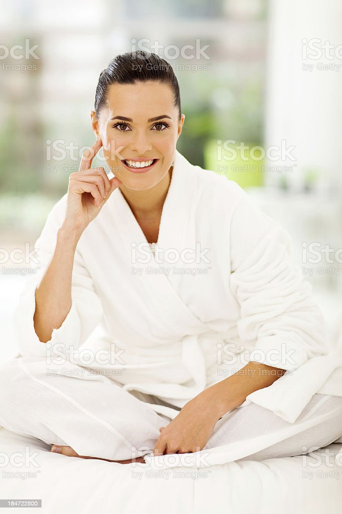 attractive woman wearing white bathrobe sitting on bed royalty-free stock photo