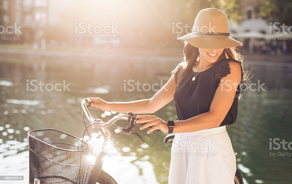Attractive woman with bike at park stock photo