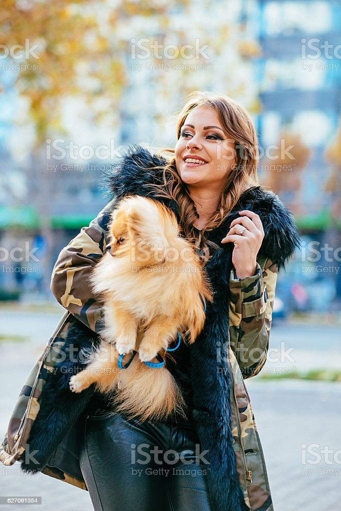 Attractive woman with dog in city stock photo