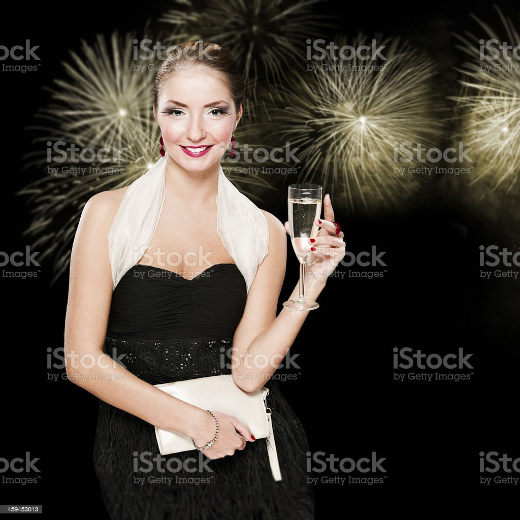 Attractive woman with glass of champagne against fireworks, black background stock photo