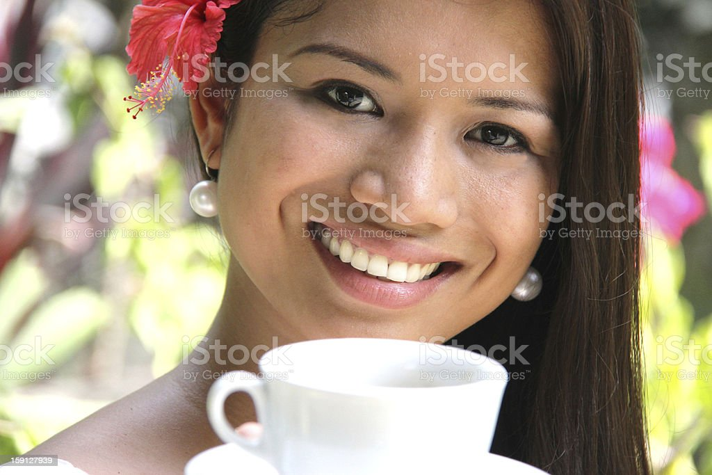 attractive woman with hibiscus flower holding cup and smiling royalty-free stock photo