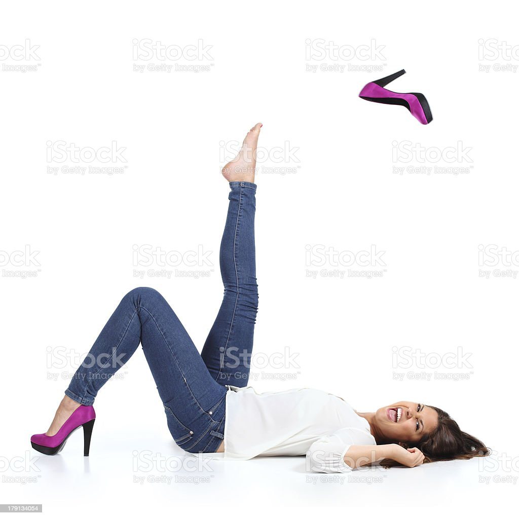 Attractive woman with jeans  throwing a fuchsia heel stock photo