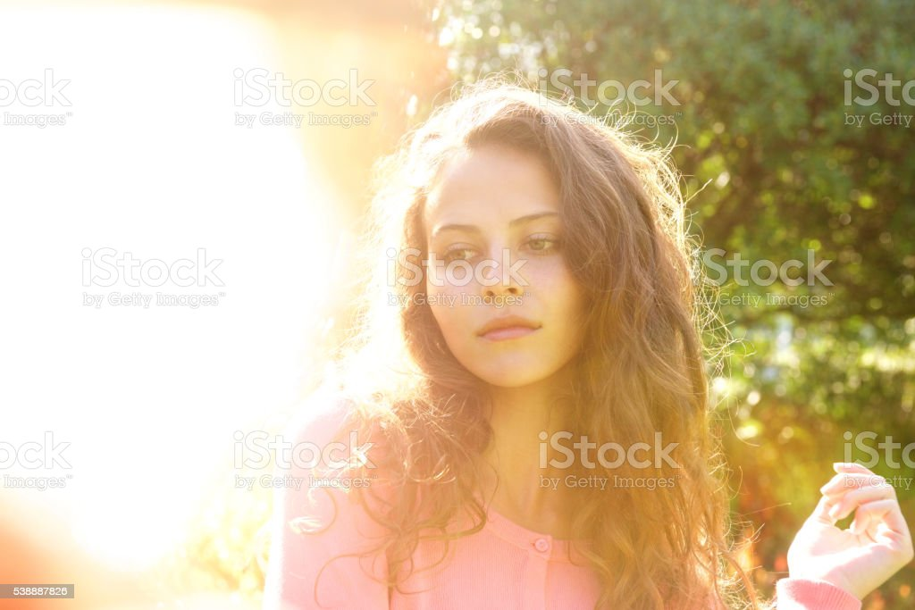 Attractive woman with long hair outside in bright sunlight stock photo