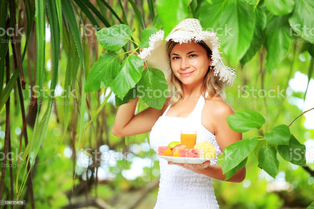 Attractive woman with plate of tropical fruits. royalty-free stock photo
