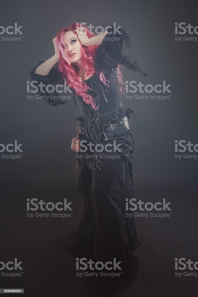 Attractive woman with red hair in witches costume, in the stock photo