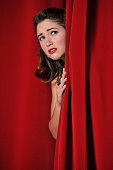 Attractive Woman with Stage Fright Hiding Behind a Curtain