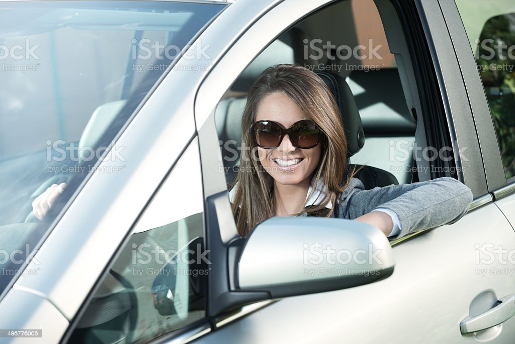 Attractive woman with sunglasses in her car stock photo