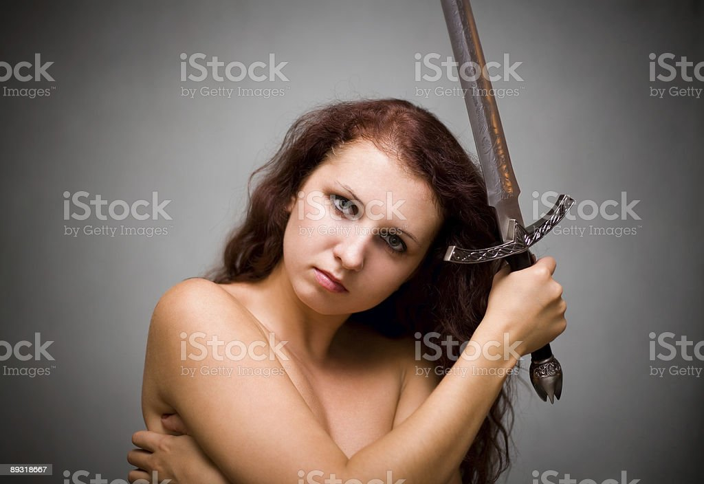 Attractive woman with sword on gray background royalty-free stock photo