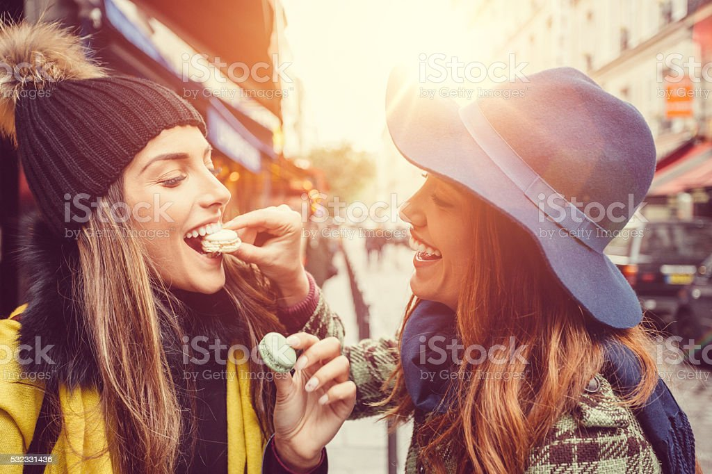 Attractive women eating parisian macaroons stock photo