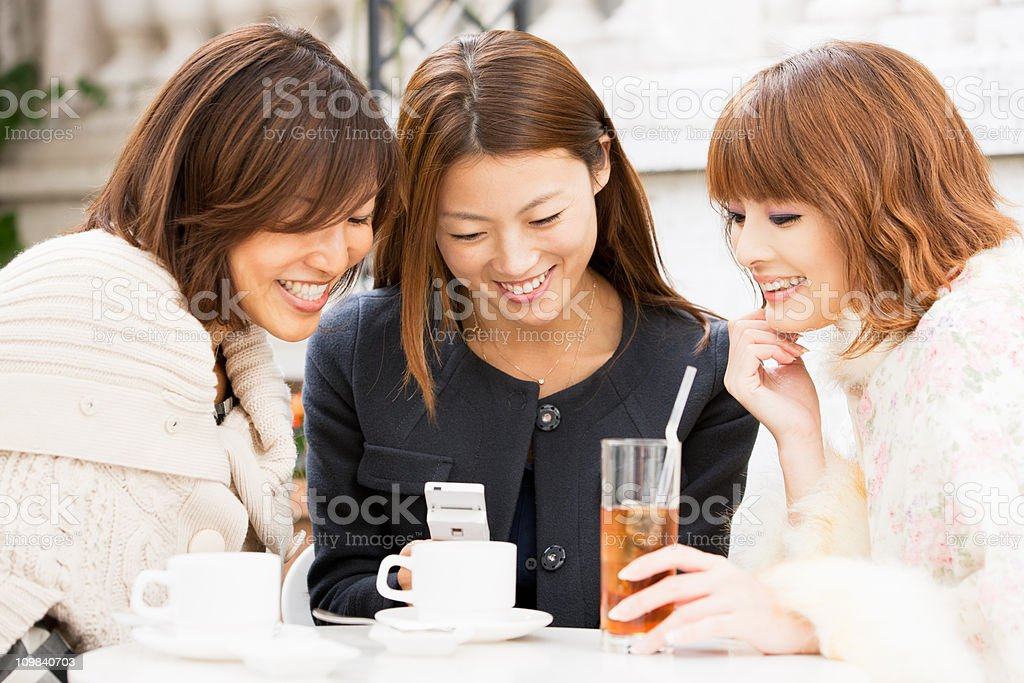 Attractive women having fun in street cafe royalty-free stock photo