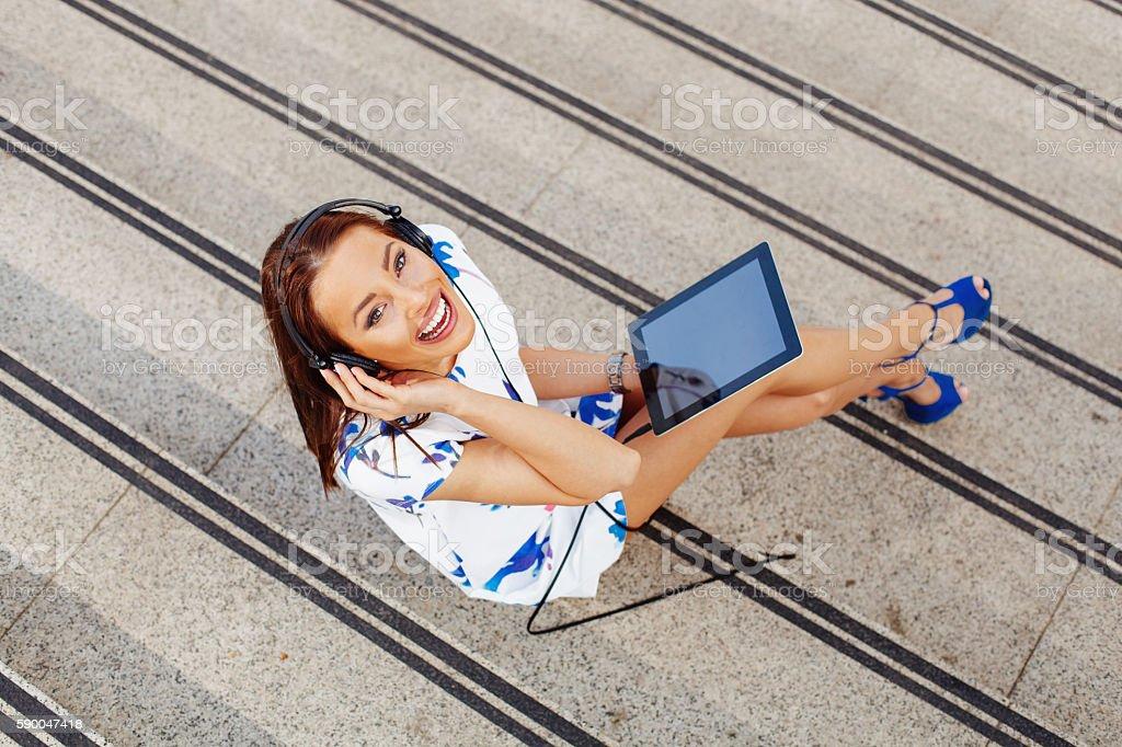 Attractive women listen to music via a digital tablet stock photo