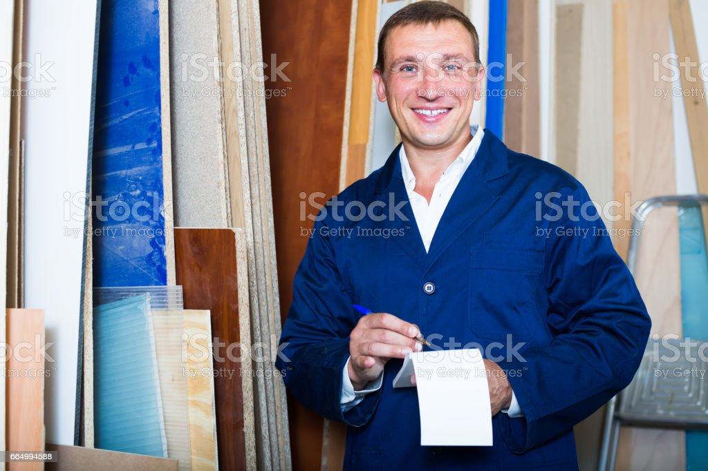 attractive workman standing with plywood pieces stock photo