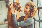 attractive young african woman playing with puppy