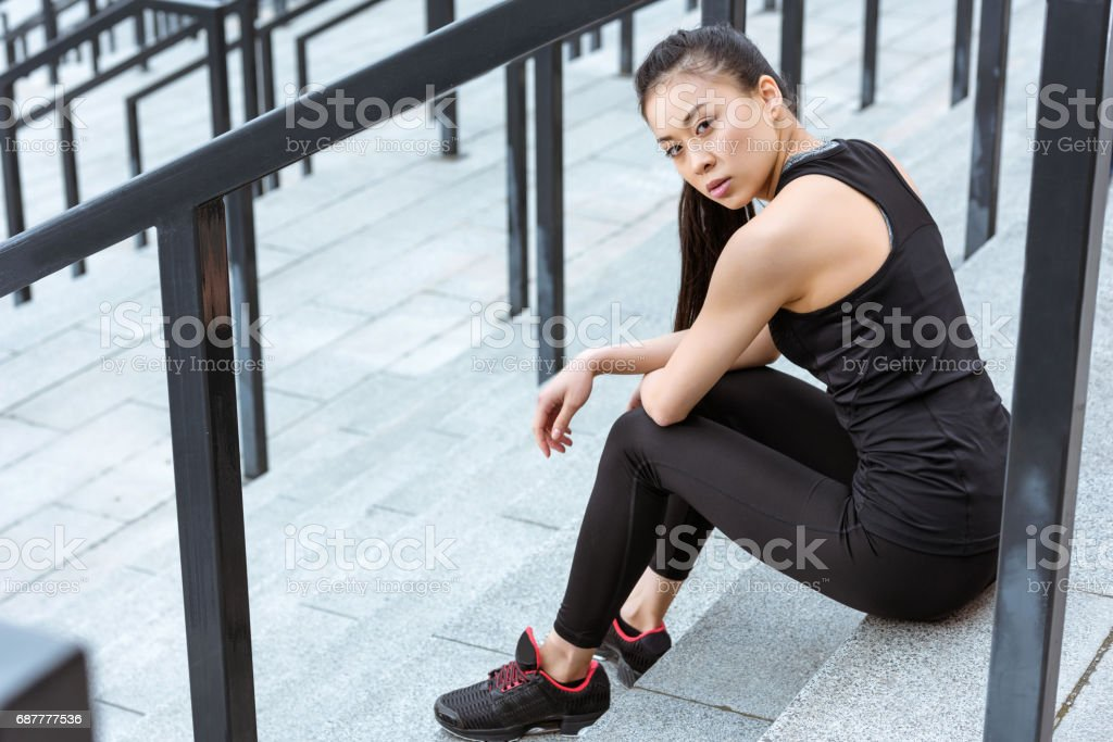 Attractive young asian sportswoman sitting on stadium stairs and looking at camera stock photo