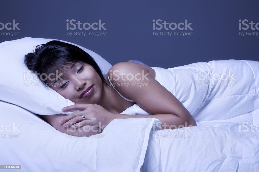 Attractive Young Asian Woman Sleeping in Bed stock photo