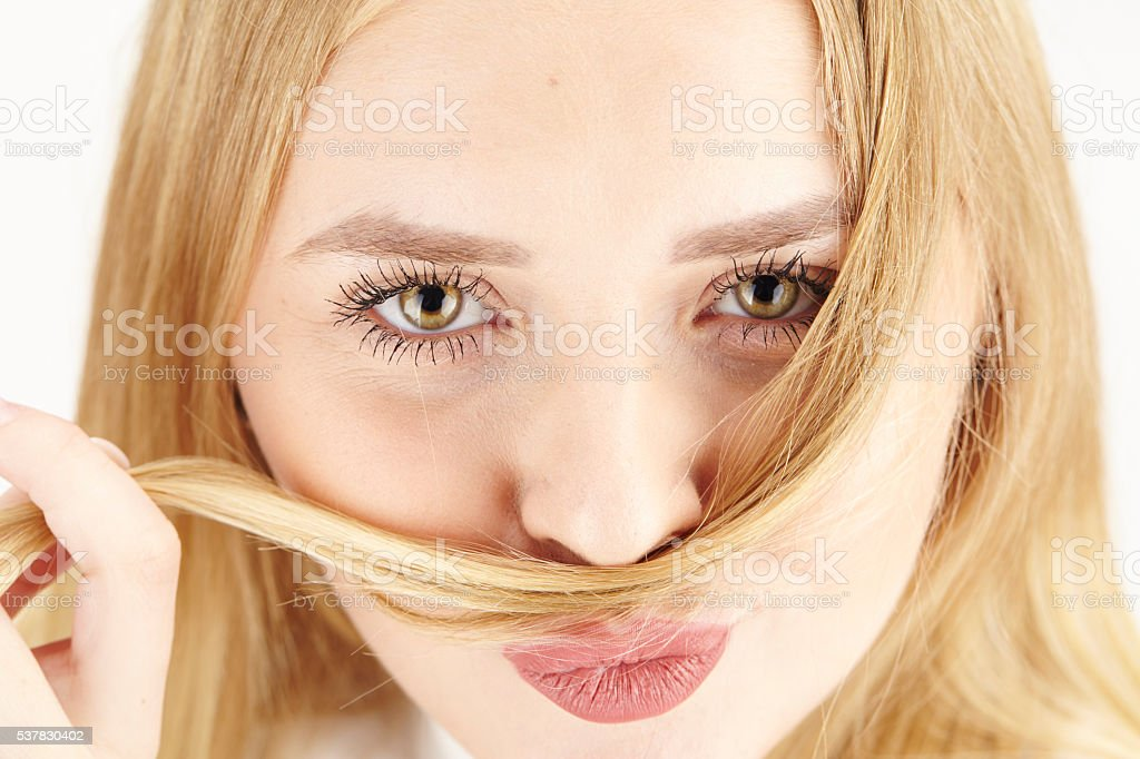 Attractive young blond woman plays with wisp of her hair stock photo