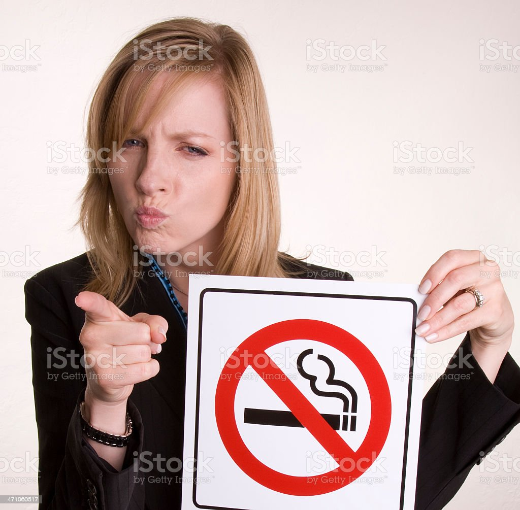 Attractive young blonde holds 'No Smoking' symbol royalty-free stock photo
