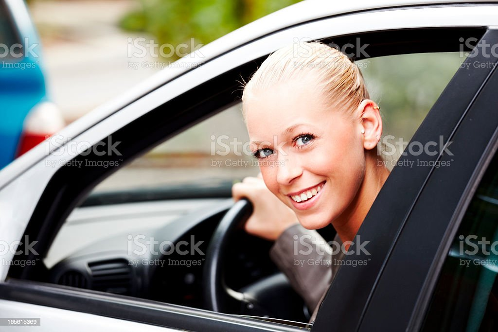 Attractive young blonde woman in her new car royalty-free stock photo
