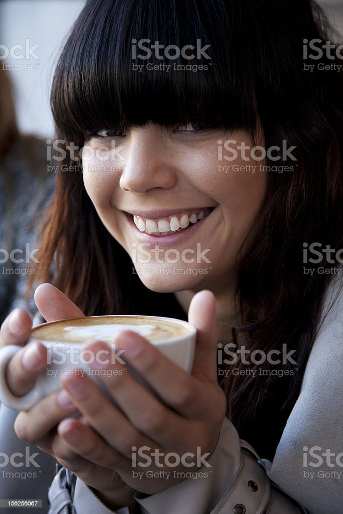 Attractive young brunette woman enjoying a coffee royalty-free stock photo