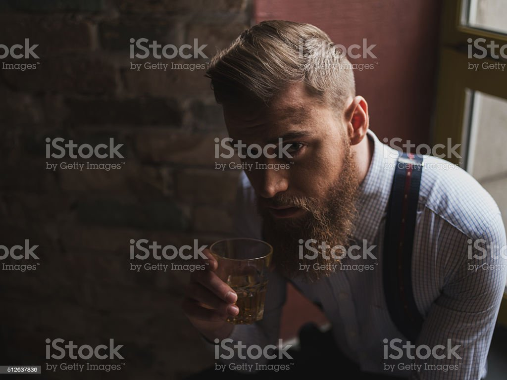 Attractive young businessman is enjoying alcohol drink stock photo