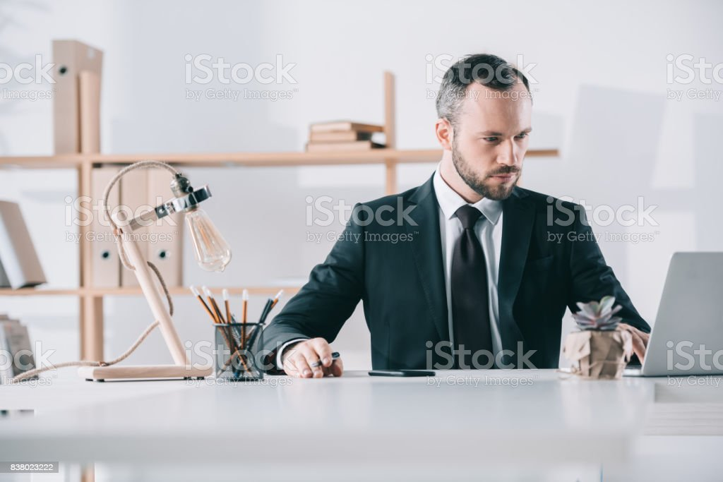 attractive young businessman looking at laptop screen stock photo