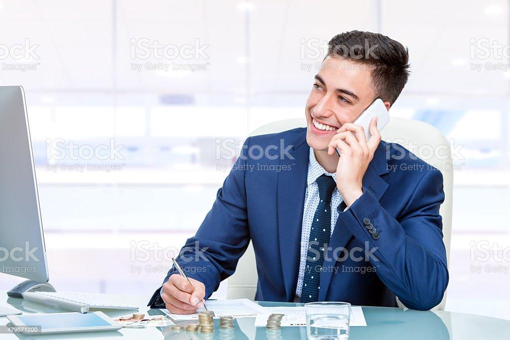 Séduisante jeune homme d'affaires, parler sur le téléphone intelligent dans le bureau photo libre de droits