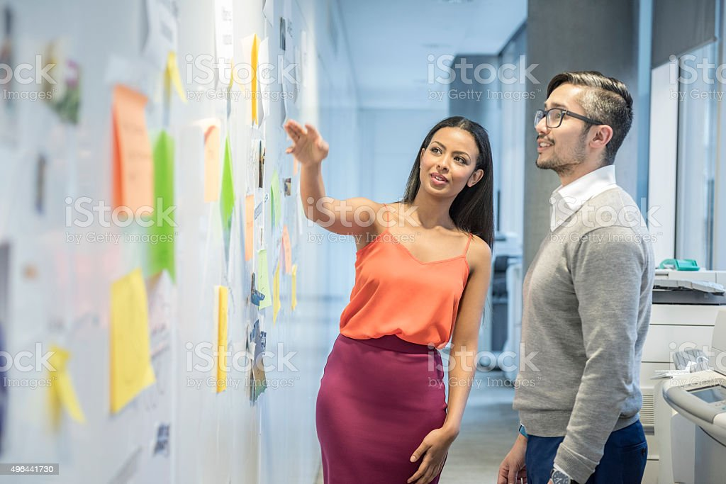 Attractive young businesswoman discussing with male colleague stock photo