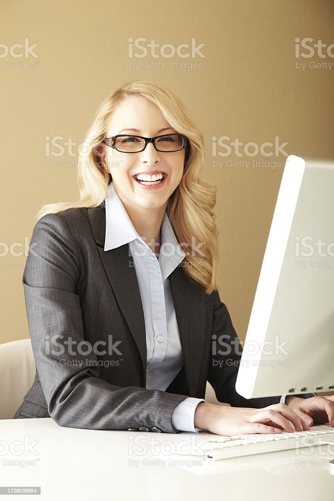 Attractive Young Businesswoman Laughing At her Desk stock photo