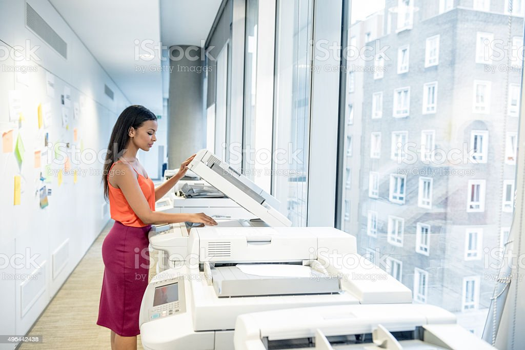 Attractive young businesswoman using photocopier in modern office stock photo