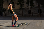 attractive young casual woman riding a skateboard