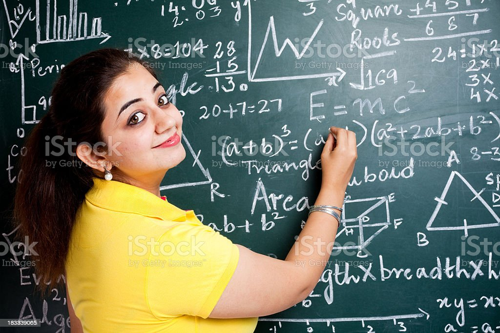 Attractive Young Cheerful Indian Mathematics Girl Teacher Classroom with Greenboard royalty-free stock photo