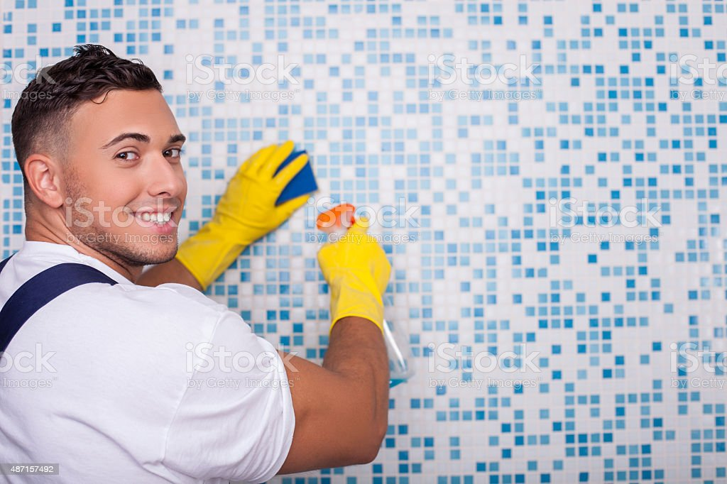 Attractive young cleaner is washing wall with a wisp stock photo