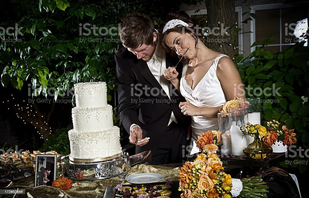 Attractive Young Couple Cutting the Wedding Cake stock photo