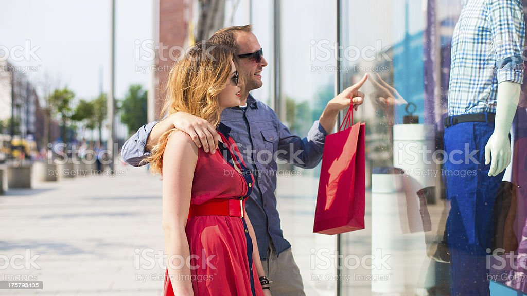 Attractive young couple looks at clothing shop display royalty-free stock photo