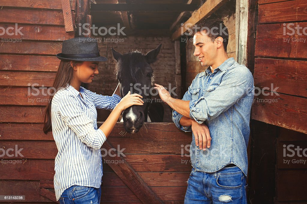 Attractive young couple stroking a black horse. stock photo