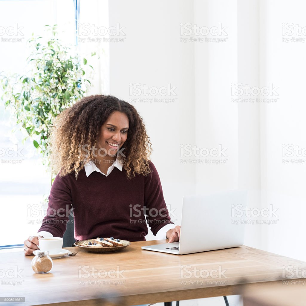 Attractive young Ethnic businesswoman working on laptop with coffee stock photo