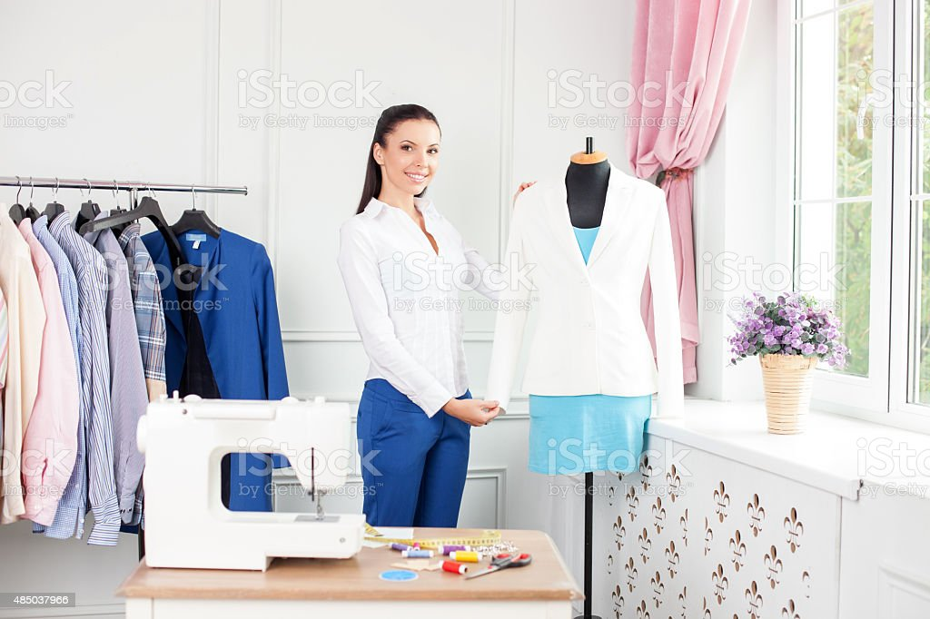 Attractive young fashion worker is projecting new clothing stock photo
