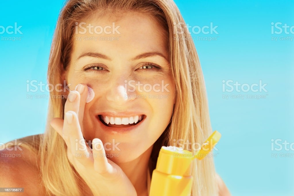 Attractive young female applying sunscreen to face stock photo