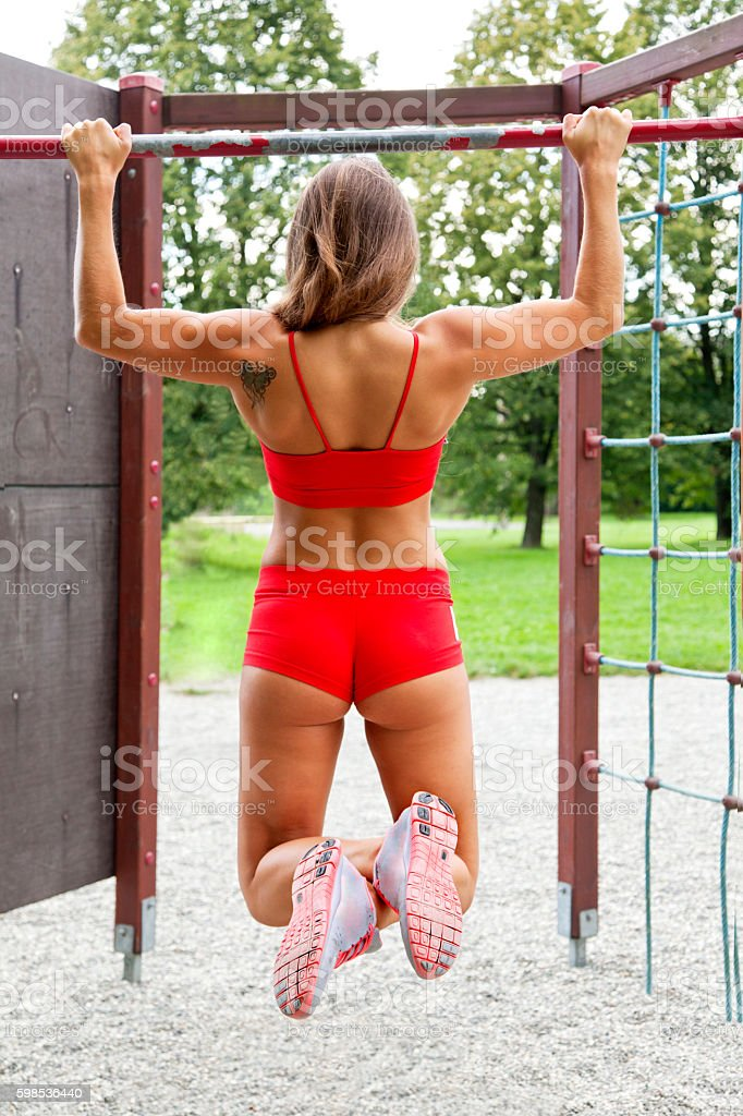 Attractive young female bodybuilder practicing outdoor on horizontal bar stock photo