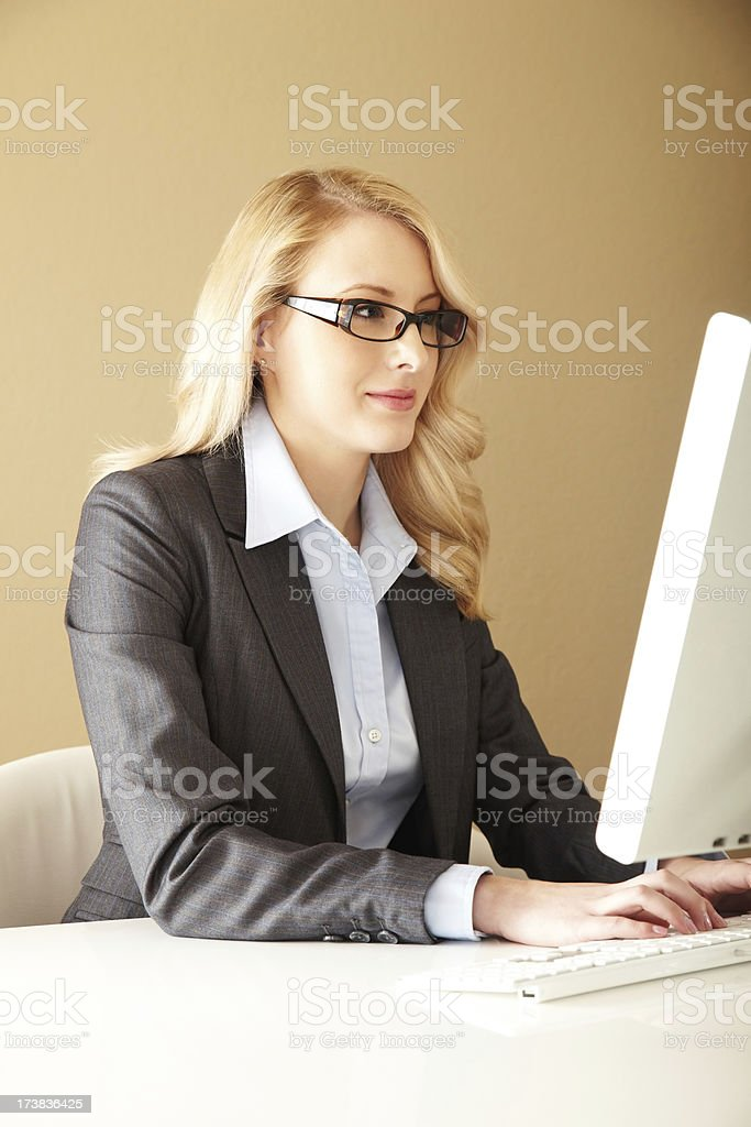 Attractive Young Female Businesswoman Typing at a Computer royalty-free stock photo