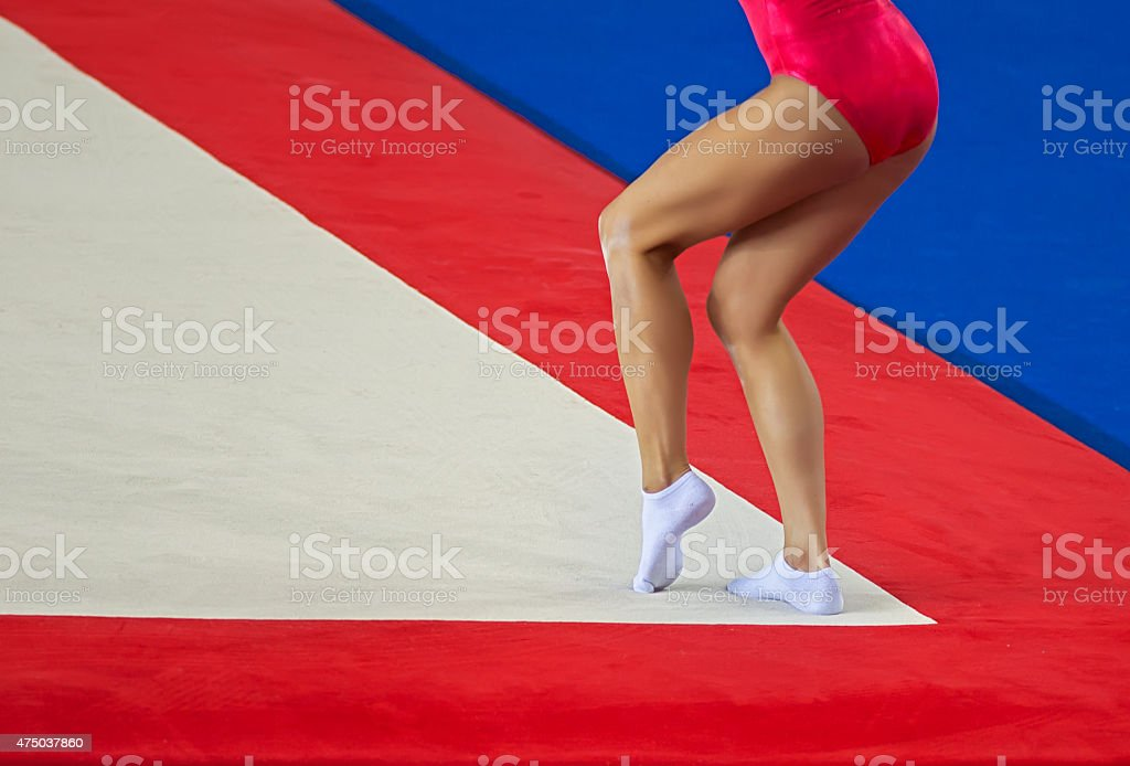 Attractive young female gymnast performs on floor stock photo