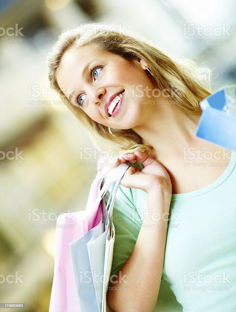Attractive young female holding shopping bags and looking away royalty-free stock photo