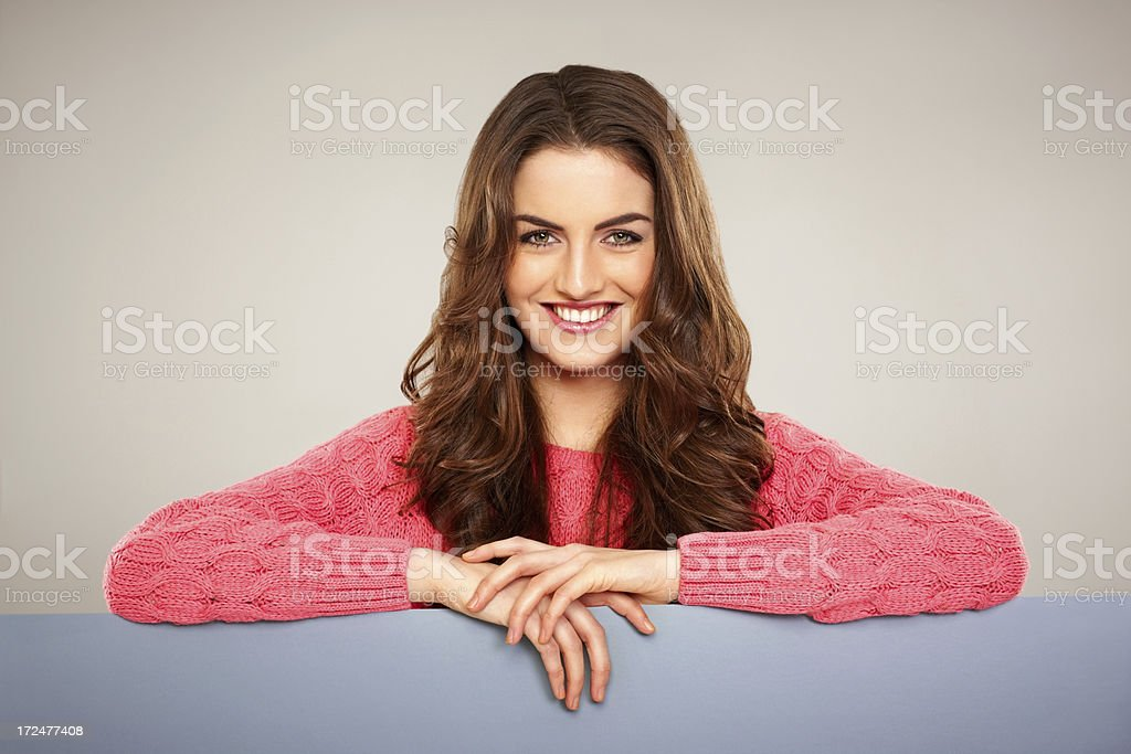 Attractive young female leaning on billboard royalty-free stock photo
